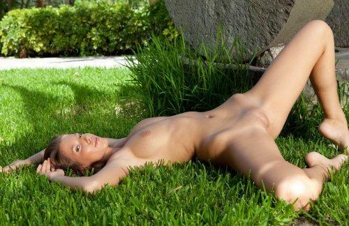 Красивая сексуальная фотомодель Lizzie позирует обнажённая на лужайке