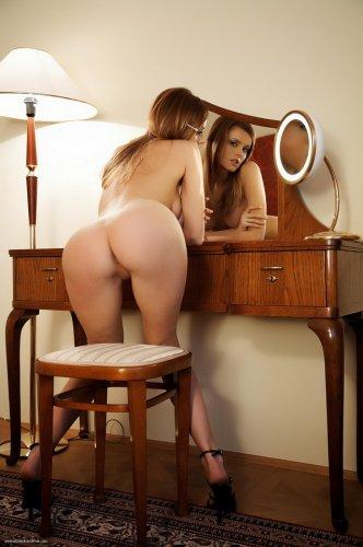 Рыженькая развратница фотографируется обнажённая возле зеркала