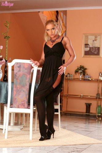 Стриптизёрша Кэти в чёрных чулках сексуально нагибается у стула в гостиной