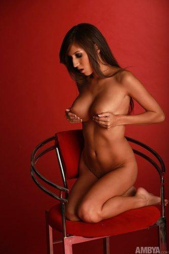 April O'Neil снимает лифчик и показывает красивую пышную грудь на стуле