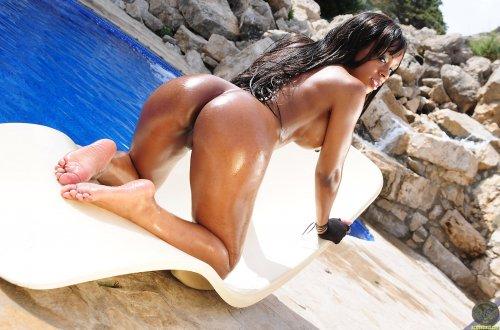 Намазанная маслом Claudia сексуально снимает купальник возле бассейна