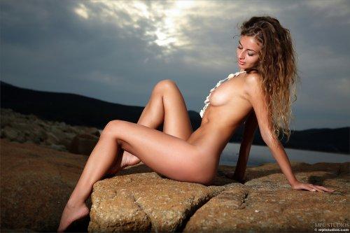 Кудрявая красивая девушка Саша фотографируется голая в сумерках на каменном берегу