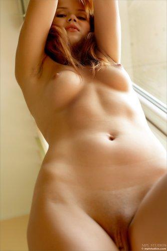 Красавица Kami с гладкой вагиной позирует обнажённая у большого окна