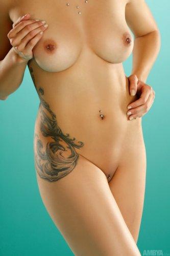 Обнажённая Tangent с большими татушками на теле и пирсингом делает эро фото