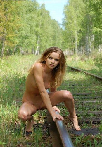 Симпатичная голая деваха делает частные эротические фото на железной дороге