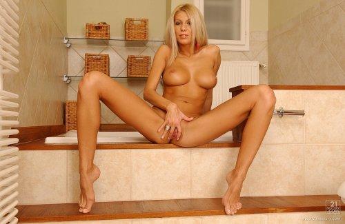 Возбуждённая стройная блондинка Clara мастурбирует в ванной на фото