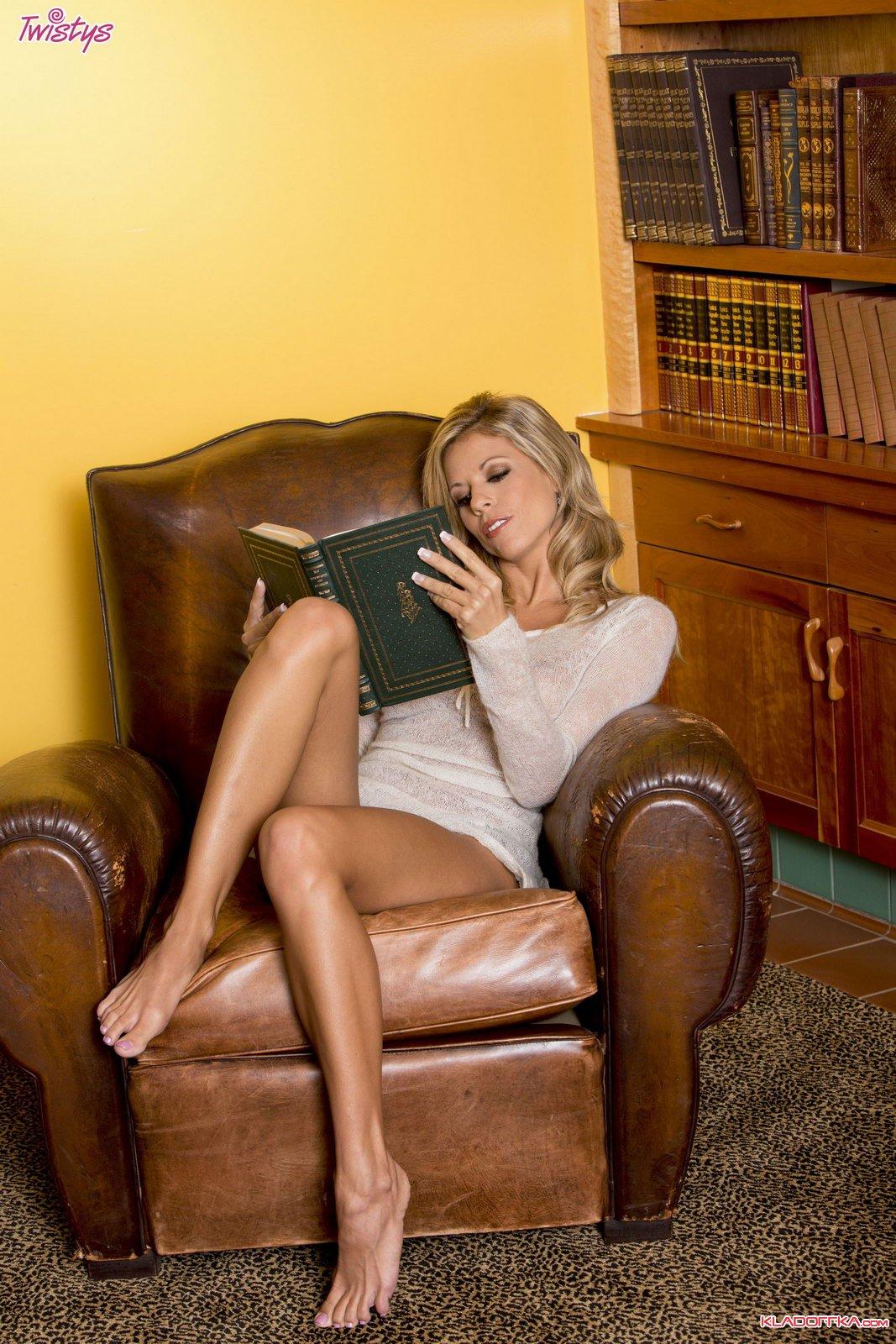 Красивая блондинка в чулках раздевается в библиотеке