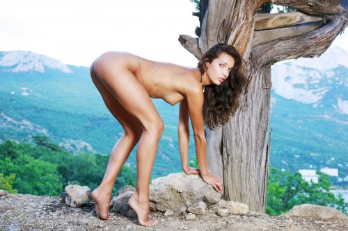 Голая зеленоглазая Ольга с красивой фигурой эротично позирует в лесу