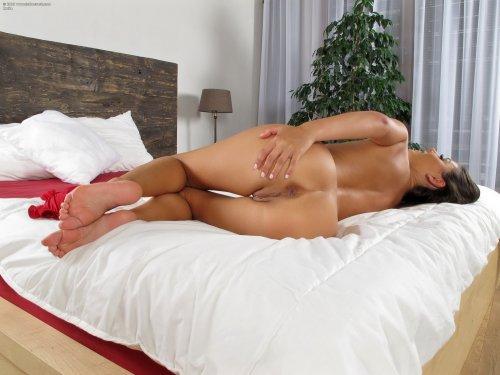 Возбуждённая Iwia в красном эротическом белье развлекается с фалосом в кровати