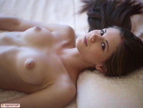 Молодая стройная модель Caprice мастурбирует лёжа на кровати для студии Hegre-Art