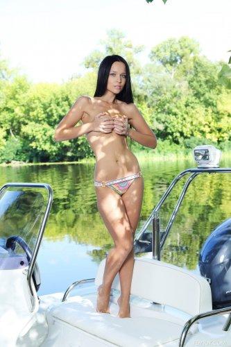 Загорелая голая любовница с подтянутой попкой Angie C раздевается на катере