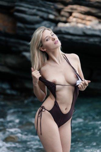 Хорошенькая молодая модель Anna Tatu без купальника на каменистом пляже