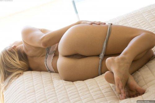 Красивая фотомодель Ryan Ryans раздевается на кровати