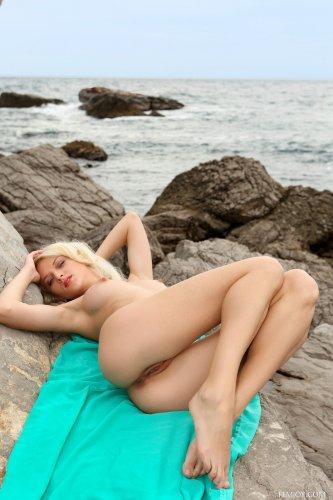 Блондинка Nika N снимает откровенный голубой купальник на скалистом берегу